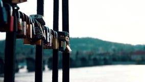 De slotsloten hangen van traliewerk naast Charles Bridge die liefde, vriendschap vertegenwoordigen en Romaans stock video