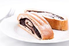 De smakelijke die cakes van het cacaobroodje met suiker op een plaat met een vork worden bestrooid, op witte achtergrond wordt ge Stock Fotografie