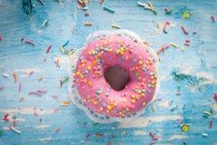 De smakelijke doughnut met roze suikerglazuur en kleurrijk bestrooit royalty-vrije stock foto