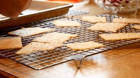De smakelijke eigengemaakte Kerstmiskoekjes worden overgebracht van bakseldienblad aan het koelen van rek stock footage