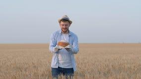 De smakelijke geur van brood, jonge mens houdt vers gebakken brood in zijn hand, ruikt het en stelt met handuitgestrektheid voor  stock footage