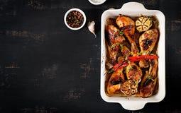 De smakelijke oven bakte gouden kippentrommelstokken in een bakselschotel stock foto