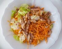 De smakelijke salade met sla, tonijnvissen, sneed wortelen, linnenzaden, olijfolie en balsemieke azijn op een witte ceramische ko Stock Fotografie