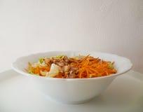 De smakelijke salade met sla, tonijnvissen, sneed wortelen, linnenzaden, olijfolie en balsemieke azijn op een witte ceramische ko royalty-vrije stock foto