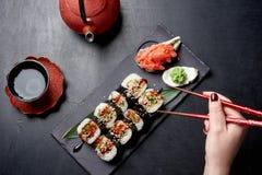 De smakelijke sushi rollen op zwarte steenplaat en Japanse sause met gember en wassabi Chinese Cousine stock fotografie