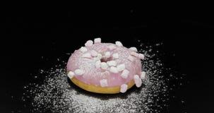 De smakelijke verse doughnut legt op zwarte oppervlakte met het poeder van de suikerglazuursuiker royalty-vrije stock afbeelding