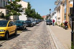 De smalle Europese die keistraat met baksteenstoepen voerde met huizen en auto's op de stoep worden geparkeerd royalty-vrije stock afbeelding