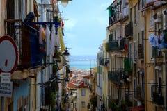De smalle steeg van Lissabon met oude woningbouw en drogende doeken stock afbeeldingen