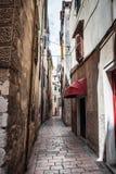 De smalle straat in de stad met oude gebouwen die in de afstand achteruitgaan royalty-vrije stock foto