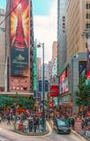 De smalle straten van Hong Kong zijn overvol met mensen Cityscape met wolkenkrabbers Verticale mening stock fotografie