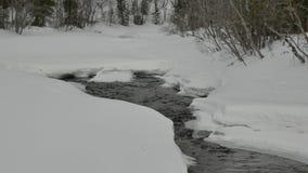De smalle stromen van de waterstroom tussen massa's van witte sneeuw stock footage