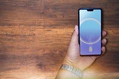 De smartphone van de handholding en vingeraftasten aan login apparaat stock foto's