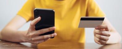 De smartphone van de vrouwenholding en creditcard met online het winkelen royalty-vrije stock afbeelding