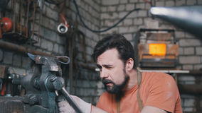 De smid buigt metaalmes met klacht in workshop smeedt, portret Stock Foto