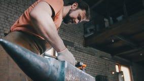 De smid buigt metaalmes met klacht in workshop smeedt, portret Stock Foto's