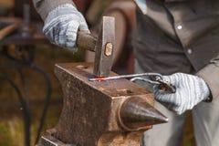 De smid die aan metaal op aambeeld werken bij smeedt het schot van het hoge snelheidsdetail Stock Fotografie