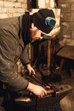 De smid smeedt een heet metaal op het aambeeld met een hamer stock foto's