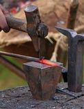 De smid smeedt een spijker met een hamer op het aambeeld Stock Foto's