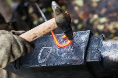 De smid smeedt ijzergesp met hamer op aambeeld Stock Afbeelding