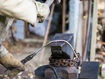 De smid smeedt ijzerstaaf op een aambeeld Stock Fotografie