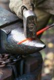 De smid smeedt roodgloeiende staalstaaf op aambeeld Stock Afbeeldingen