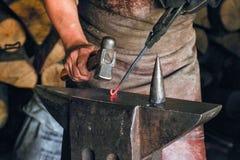 De smid verwerkt een heet metaalvoorwerp van een spiraalvormige vorm bij aambeeld in een workshop stock foto