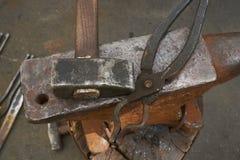 De smids` s hulpmiddelen zijn een aambeeld, een hamer en scharen Stock Afbeeldingen
