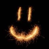 De smiley de sourire étrange heureux dessiné avec des étincelles sur le fond noir Photographie stock