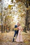 De Smilngjonggehuwden koesteren onder een val van de herfstbladeren royalty-vrije stock afbeelding