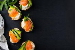 De snacks, bruschetta met roomkaas, avocado en zalm, leggen boven vlak stock foto