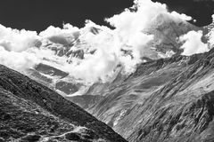 De sneeuw behandelde bergbovenkant in wolken wordt overspoeld die Royalty-vrije Stock Afbeeldingen
