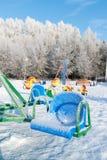 De sneeuw behandelde schommeling en dia bij speelplaats Stock Foto
