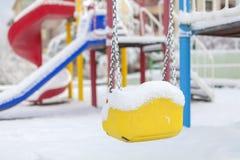 De sneeuw behandelde schommeling en dia bij speelplaats in de winter Stock Foto's