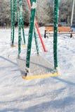 De sneeuw behandelde schommeling en dia binnen bij speelplaats Stock Afbeelding