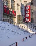 De sneeuw behandelde trap met een zonovergoten deel van een grijs gebouw, Tchang-tchoun, China Stock Foto