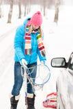 De sneeuw die van de vrouw zich met de kettingen van de autoband bevindt Royalty-vrije Stock Afbeelding