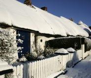 De sneeuw met stro bedekt plattelandshuisje Stock Afbeelding