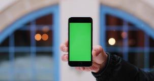 De sneeuw valt over een de holdingssmartphone van de mensen` s hand met het groene scherm in zijn wapen