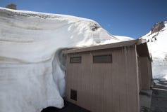 De sneeuw wikkelt de bovenkant van een bijgebouw Stock Foto's
