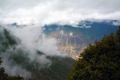 De sneeuwbergen van Kawakarpo door wolk worden behandeld die Stock Afbeeldingen