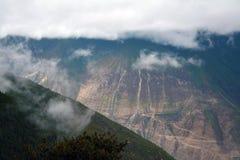 De sneeuwbergen van Kawakarpo door wolk worden behandeld die Stock Foto's