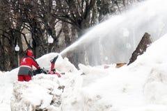 De sneeuwblazer maakt de straat van sneeuw schoon Stock Foto