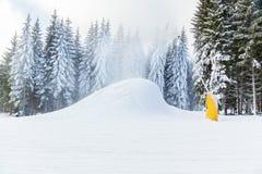 De sneeuwkanonnen die van de skitoevlucht in de sneeuw en van bomeninii winter h lopen Royalty-vrije Stock Afbeeldingen