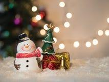 De sneeuwman heel om te glimlachen vieren en de doos bokeh achtergrond Stock Fotografie