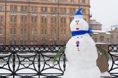 De sneeuwman op de winterdijk, Kerstmisdecoratie in de stad Nieuwjaarviering in St. Petersburg, Rusland tijdens sneeuwval stock afbeelding