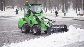 De sneeuwploeg verwijdert heel wat sneeuw bij de sneeuwval stock videobeelden