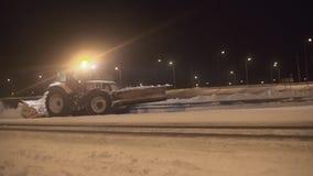 De sneeuwploegtractor ontruimt sneeuw van de rijweg stock videobeelden