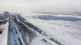De sneeuwwinter in mooie stad of stad klem Hoogste mening van bevroren rivier, vele auto's over weg, oude gebouwen charming stock footage
