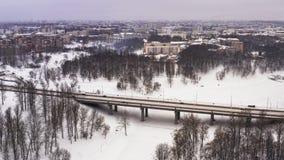 De sneeuwwinter in mooie stad of stad klem Hoogste mening van bevroren rivier, vele auto's over weg, oude gebouwen charming stock video
