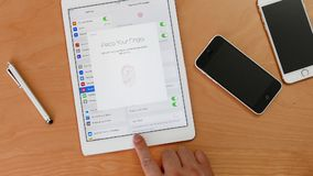 De snelle motie van de mens plaatst - omhoog de vingerafdrukscanner op een ipad met twee iphones stock videobeelden